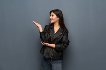 Teenager girl over grey wall extending hands to the side for inviting to come