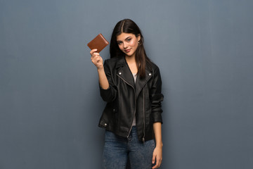 Teenager girl over grey wall holding a wallet