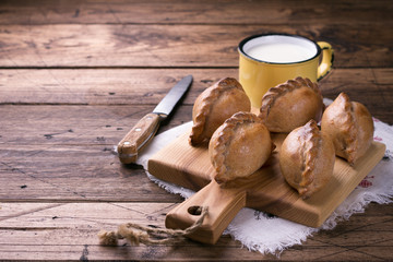 Russian traditional rye pies with egg, kokurki, on a wooden table