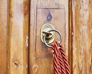 vintage key lock on brown solid wood door closeup with red cord