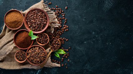 Ground coffee and coffee beans. Assortment of coffee varieties on a black background. Top view. Free space for your text.
