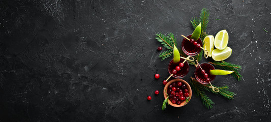 Alcoholic liqueur from a cranberry in a glass. Cranberry, lime, rosemary. On a rustic background. Top view. Free space for your text.