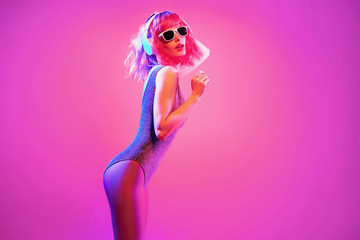 Fashion contemporary neon style. Young graceful woman in party DJ bodysuit dance. Disco summer vibes. Adorable fashionable sexy girl, pink hair, trendy makeup. Creative art pink neon color