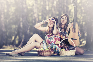 Two young fashion girls with fruit baskets in summer forest