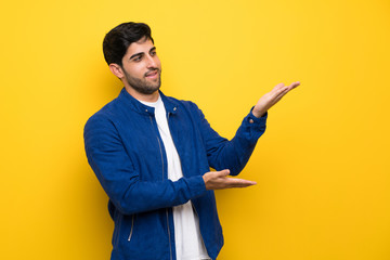 Man with blue jacket over yellow wall extending hands to the side for inviting to come