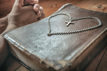 Close up of cross necklace on bible with a man praying. symbol of christian concept.