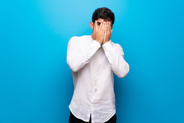 Young man over isolated blue wall covering eyes by hands and looking through the fingers