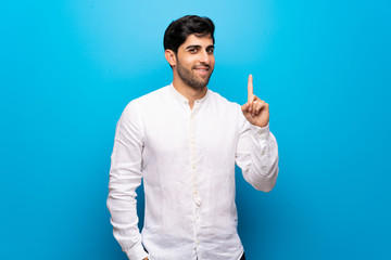 Young man over isolated blue wall showing and lifting a finger in sign of the best Wall mural