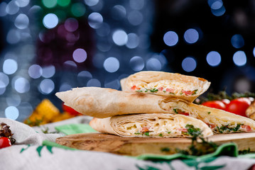 Burrito with meat and vegetables on a wooden board and napkins against a blue blurred beautiful Christmas garland. close up. space