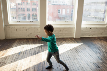 High angle view of boy with hand raised dancing on hardwood floor against windows at home
