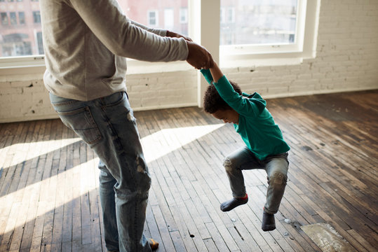Low section of playful father spinning son on hardwood floor at home