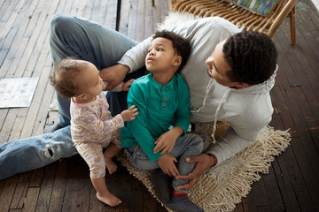 High angle view of father playing with children while relaxing on hardwood floor at home