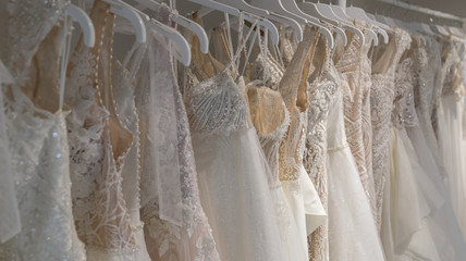 Wedding dresses hang on hangers. Factory of wedding dresses.