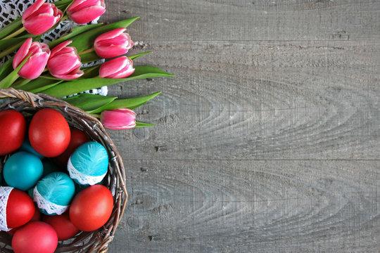 Wielkanocne tło z różowo-białymi tulipanami i kolorowymi pisankami w koszyku
