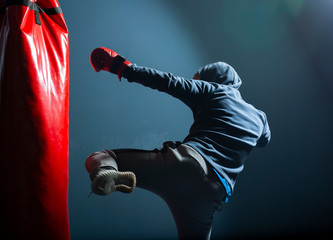 The young man workout a kick on the punching bag