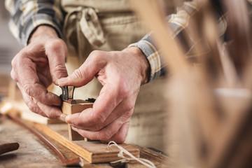 Hände eines Instrumentenbauers bei der Arbeit mit dem Geigenbogen