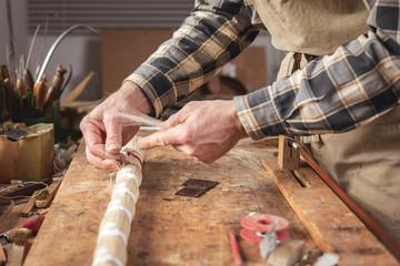 Geigenbauer verwendet Pferdehaar für den Geigenbogen