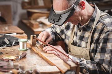 Instrumentenbauer bei Präzisionsarbeit am Geigenbogen