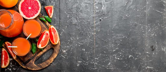 Wall Murals Juice Juice of ripe grapefruit in a jug on a cutting Board.