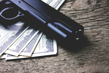 a gun with money on a wooden table