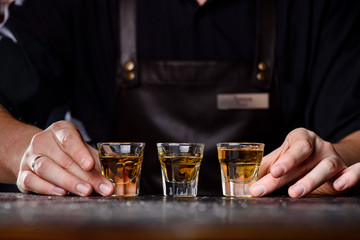 Bartender in a dark leather apron puts three glasses of whiskey on a dark wooden bar in a nightclub. Close-up. Spa ce