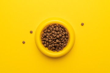 yellow pet bowl full of dry food on the yellow background