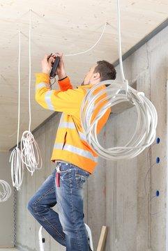 Elektriker arbeitet und installiert in einem Neubau
