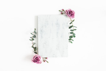 Flowers composition. Paper blank, eucalyptus branches and rose flowers on white background. Wedding invitation card. Flat lay, top view, copy space