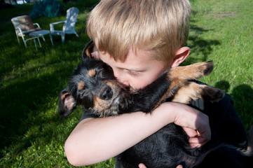 Boy kissing his dog outdoors