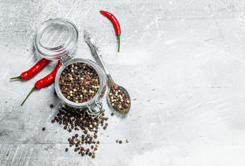 Pepper peas in a glass jar with a spoon and red pepper.