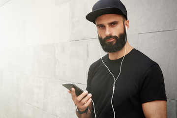 Hispanic young confident man stands in light street in front of wall, changes songs and tracks on smartphone, listens to music in earphones. Hipster with beard.