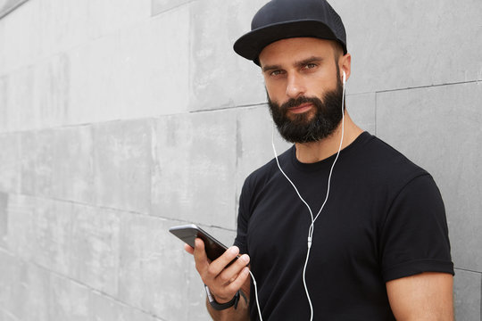 Confident bearded male with dark Snapback Cap wearing casual clothes is standing with a mobile phone in his hand on concret wall background.Model look hipster is talking on a smartphone via earphones