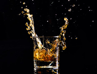 whiskey with splash on black background, brandy in a glass