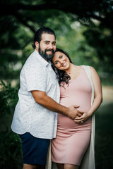 Portrait of man touching his pregnant wife's belly while standing outdoors