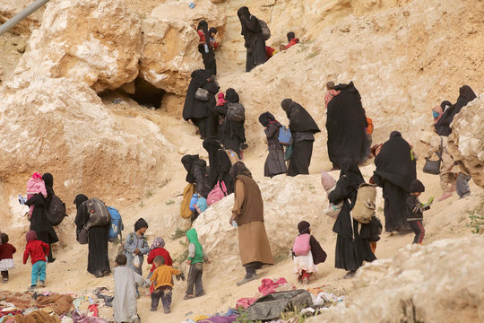 Families of Islamic state militants walk as they surrendered in the village of Baghouz, Deir Al Zor province