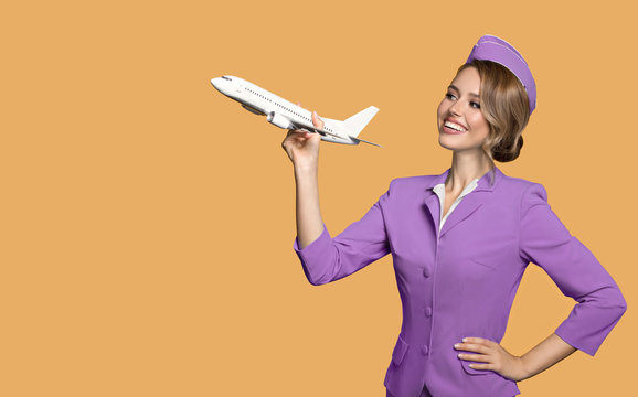 Cheerful stewardess holding airplane in hand.