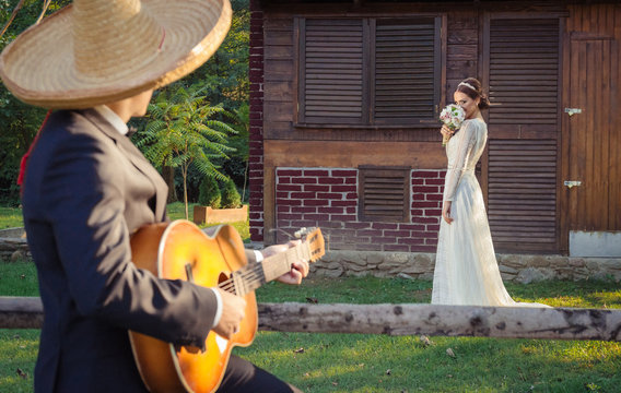 Groom with sombrero hat singing to his bride to be, playing guitar. Bride in the background holding wedding bouquet. Mexican celebration concept