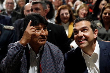 Bolivian President Evo Morales and Greek Prime Minister Alexis Tsipras chat during a conference at the Stavros Niarchos Foundation Cultural Center, in Athens