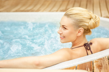 She earned this rest. Beautiful woman looking happy relaxing in the Jacuzzi