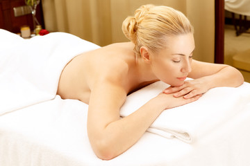 Ready to relax! Top view shot of a beautiful woman lying on the massage table in SPA therapy room