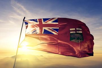 Manitoba province of Canada flag waving on the top sunrise mist fog