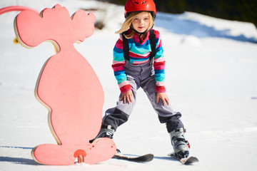 Child girl skiing in mountains. Active kid with safety helmet and goggles. Ski race for young children. Kids ski lesson in alpine school. Little skier racing in snow