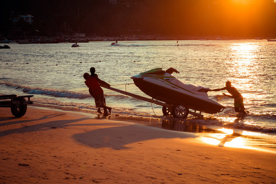 Men at sunset pull hydrocycle out of the water on a sandy beach.  Summer vacation. Water bike loaded onto a trailer