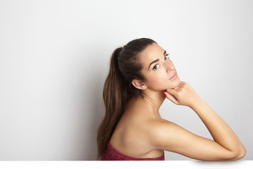 Portrait of beautiful pretty young woman with long hair looking at the camera at empty white background wall. Space for copy paste text message