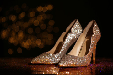 Golden glitter shoes on dark reflective surface against blurred background. Space for text Wall mural