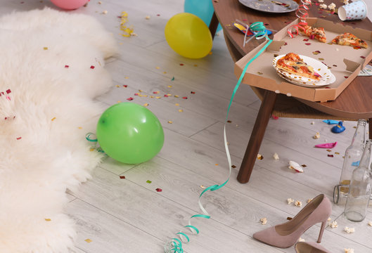 Table with pizza leftovers in messy room. After party chaos