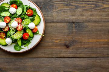 Fototapeta Vegetarian meal. Fresh vegetable salad on dark wooden background top view copy space