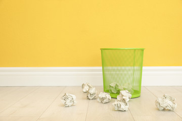 Metal bin and crumpled paper against color wall, space for text