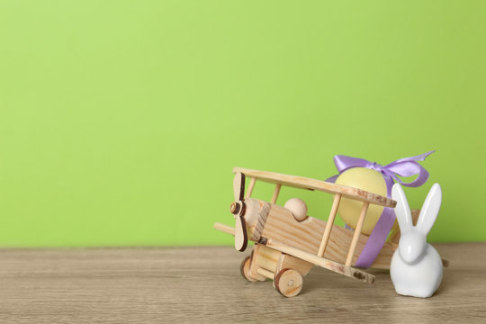 Wooden airplane with dyed egg and cute Easter bunny on table against color background, space for text
