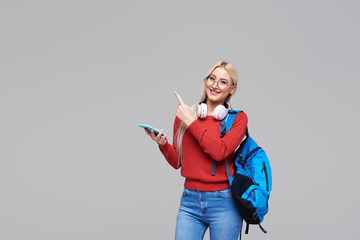 Portrait of a cheerful happy blond female student with blue backpack listening online lecture on...